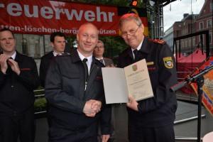 Kreisbrandmeister Wolfgang Weiden (r.) überreicht Löschzugführer Dirk Pütz die Jubiläumsurkunde